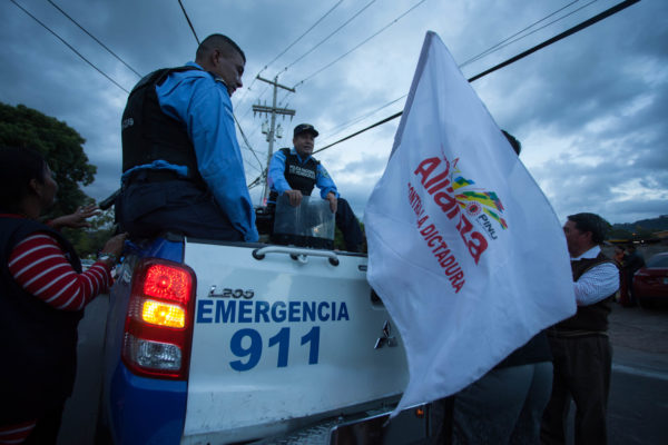 Protesters talk with police before a march in Tegucigalpa – Appeared in The Progressive