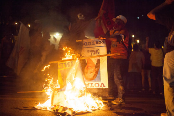 Protesters burn campaign signs for the Partido Nacional outside the US Embassy December 2017