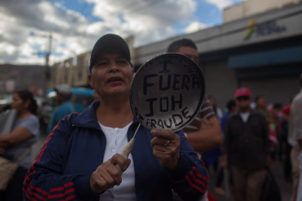 A woman bangs a pan outside congress in Tegucigalpa in protest of the re-election of Juan Orlando Hernandez February 2018
