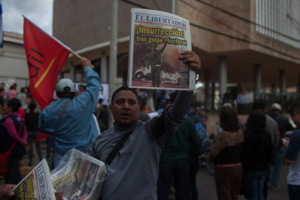 A man sells papers calling for a popular insurection in Tegucigalpa February 2018