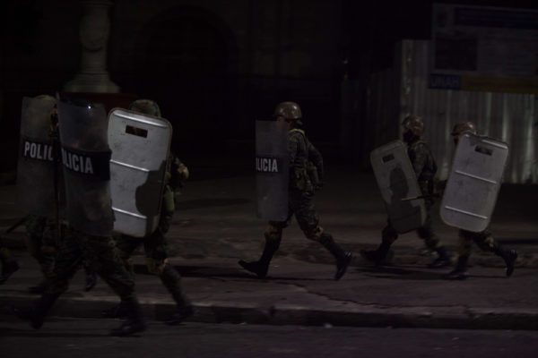 Soldiers chase protesters though the streets of Tegucigalpa February 2018